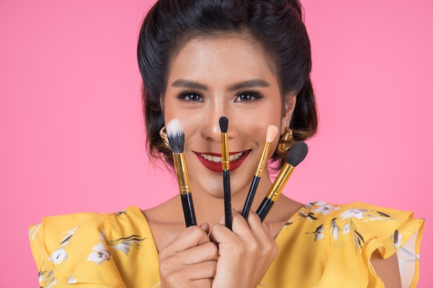 Portrait of woman with makeup brush professional show