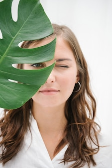 Portrait of a woman with monstera leaf