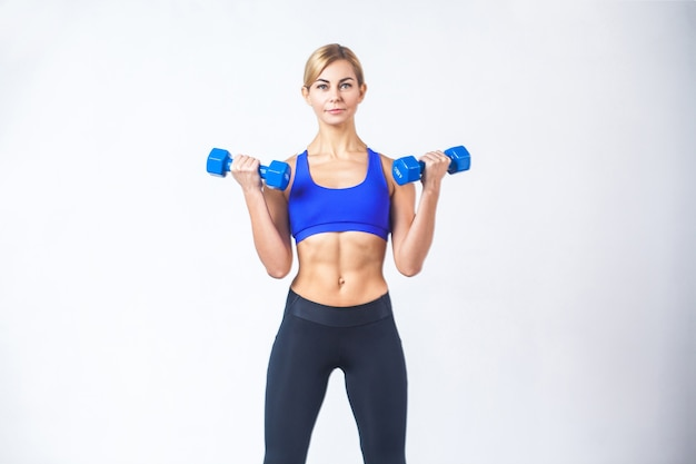Portrait of woman with perfect body, holding two blue dumbbells. indoor shot