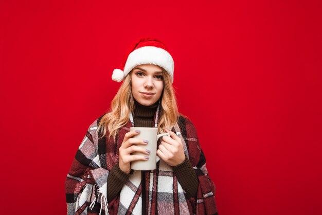 一杯のコーヒーを保持しているサンタの帽子を持つ肖像画の女性