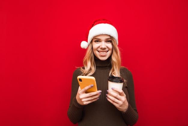 Портрет женщины в шляпе санта держит телефон