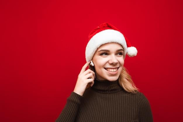 Портрет женщины в новогодней шапке, слушающей музыку в беспроводных наушниках