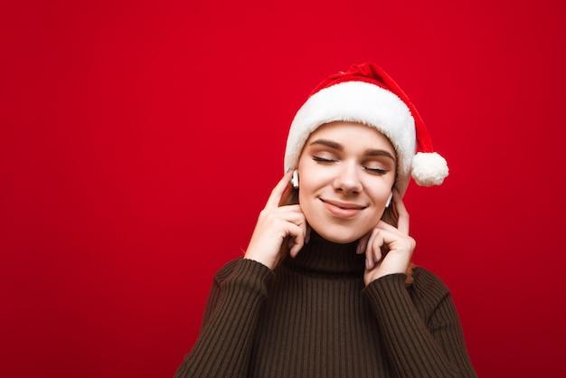 ワイヤレスヘッドフォンで音楽を聴いているサンタ帽子を持つ肖像画の女性