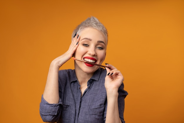 Portrait woman with short hair with make up brush in hand studio shot