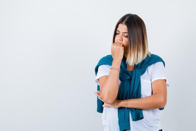 Ritratto di donna con maglione legato che morde il pugno emotivamente con una maglietta bianca e guarda una vista frontale pensierosa