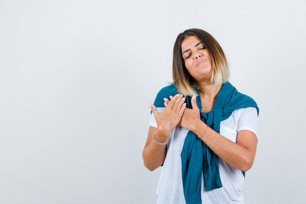 Portrait of woman with tied sweater with hands on chest in white t-shirt and looking delighted front view