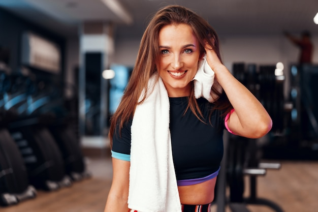Portrait of a woman with towel working out in a gym