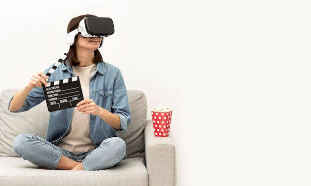 Portrait woman with virtual reality headset eating popcorn