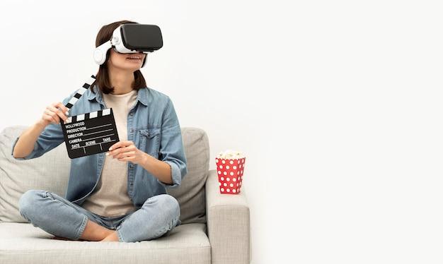 Портрет женщины с гарнитурой виртуальной реальности, едящей попкорн