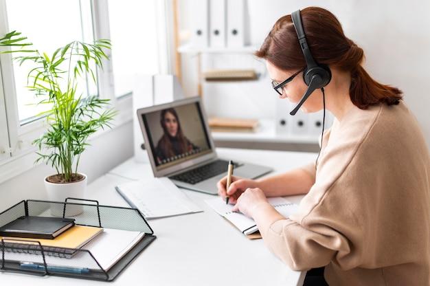 Donna del ritratto al lavoro che ha videochiamata sul laptop