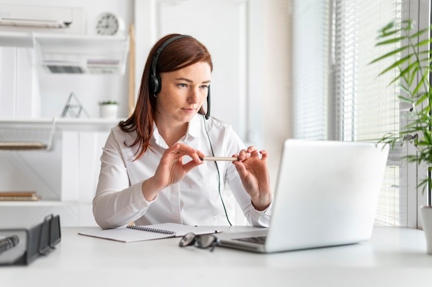 Portrait woman at work having video call on laptop