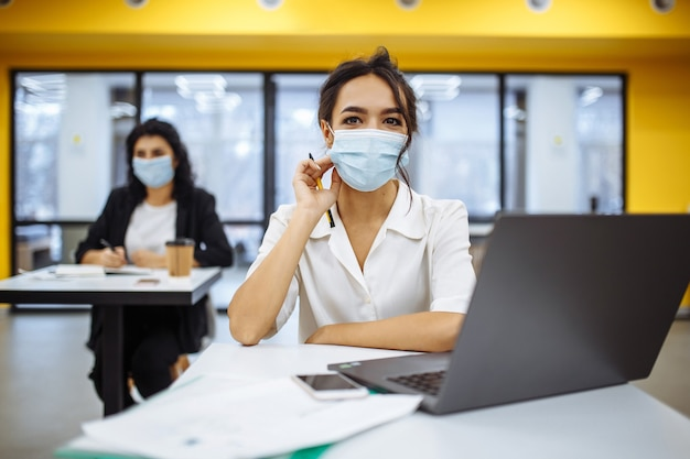 Portrait of a woman working on a laptop at an office desk, wearing medical mask and staying safe during covid-19 pandemic outbreak.