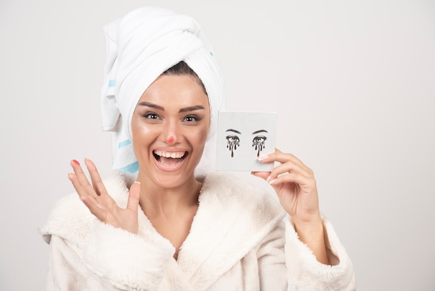 Portrait of woman wrapped in white towel with eye shadow palette