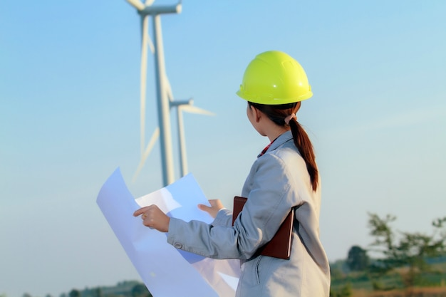 Portrait women asia engineer working and holding blueprints at wind turbine farm