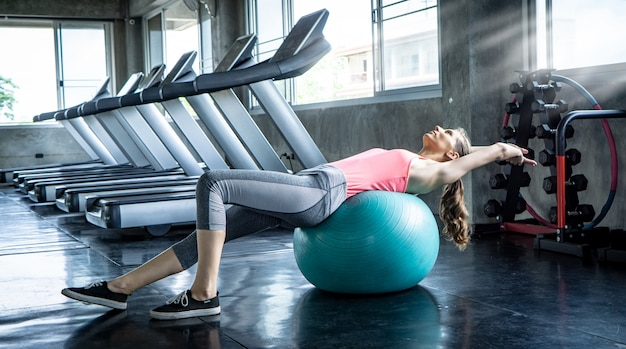 Portrait of a women exercises with ball in the gym