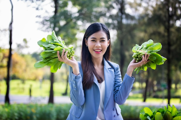 Portrait of women holding vegetable at organic plantation and checking of growing plant