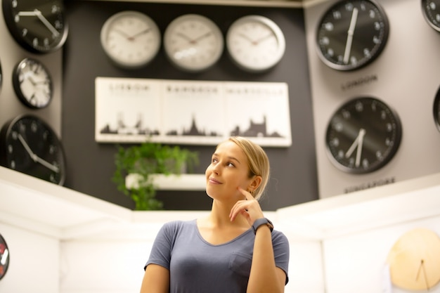 Portrait of women looking away while standing against clocks on wall