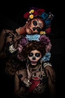 Portrait of women with a sugar skull makeup dressed with flower crown