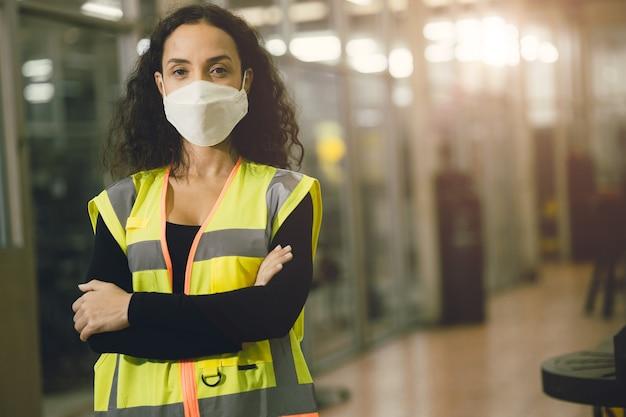 초상화 여성 노동자는 건강한 노동 관리를 위해 공장에서 코로나 바이러스 확산 및 연기 먼지 대기 오염 필터를 보호하기 위해 일회용 안면 마스크를 착용합니다.