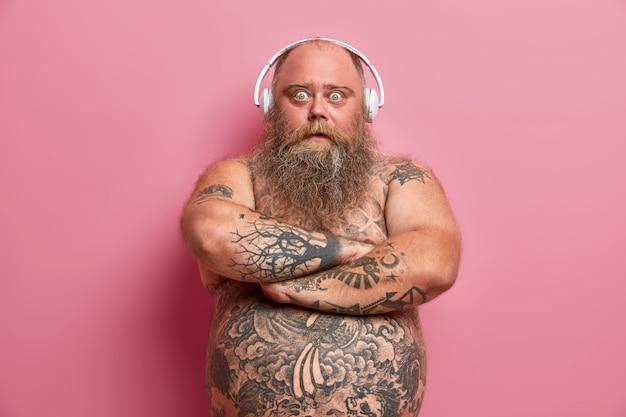 Il ritratto dell'uomo barbuto meravigliato tiene le braccia conserte, guarda con gli occhi spalancati, ha comprato le cuffie durante i saldi delle vacanze, coglie vibrazioni positive, ha la pancia nuda tatuata, obeso a causa dello stile di vita pigro
