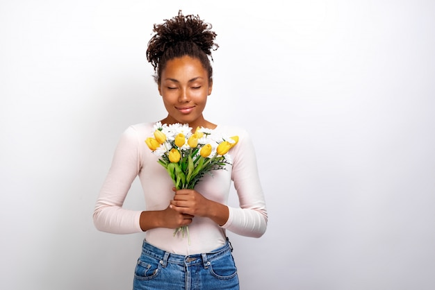 Portrait of wonderful girl with bouquet of flowers tulips and daisies in her hands