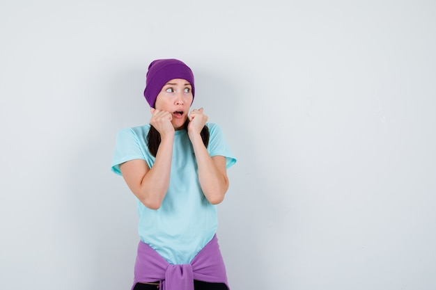 Portrait of wonderful lady keeping fists near mouth, looking aside in blouse, beanie and looking horrified front view