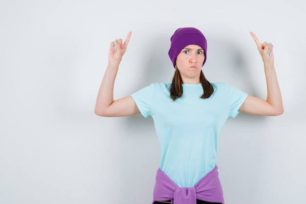 Portrait of wonderful lady pointing up in blouse, beanie and looking angry front view