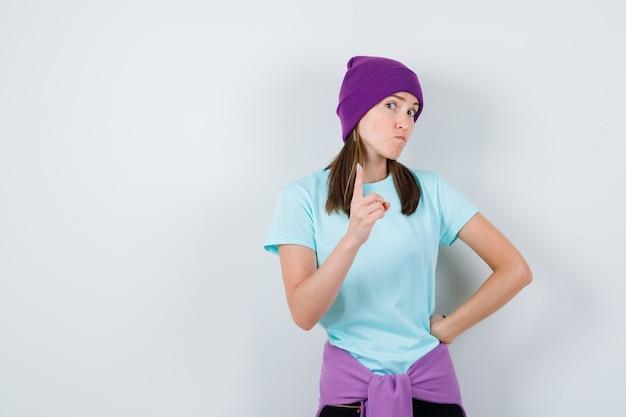 Ritratto di una donna meravigliosa che punta in alto in camicetta, berretto e sembra fiduciosa in vista frontale