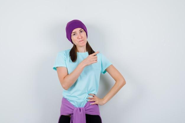 Ritratto di una donna meravigliosa che punta all'angolo in alto a destra in camicetta, berretto e sembra fiduciosa in vista frontale