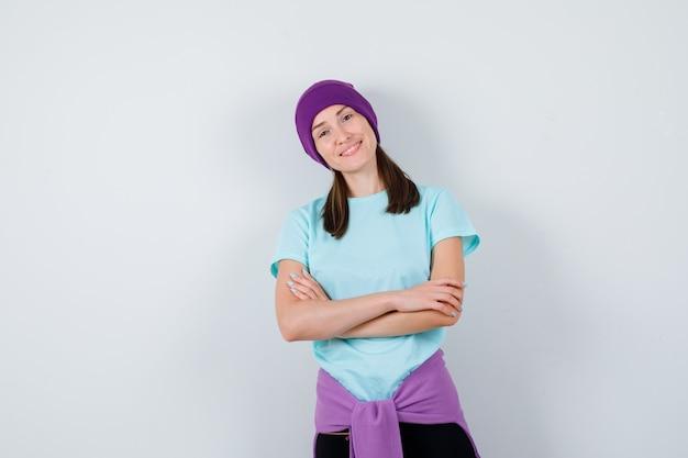 Ritratto di una donna meravigliosa con le mani incrociate in camicetta, berretto e dall'aspetto fiducioso in vista frontale