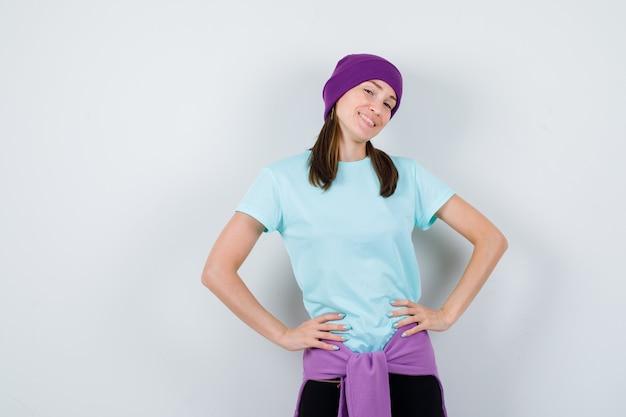 Ritratto di una donna meravigliosa con le mani sulla vita in camicetta, berretto e dall'aspetto fiducioso in vista frontale