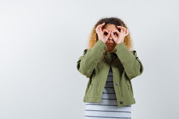 Ritratto di donna meravigliosa che mostra il gesto di occhiali in giacca verde, camicia e guardando la vista frontale focalizzata