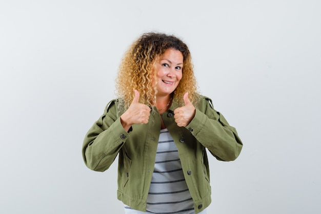 Portrait of wonderful woman showing thumbs up in green jacket, shirt and looking satisfied front view