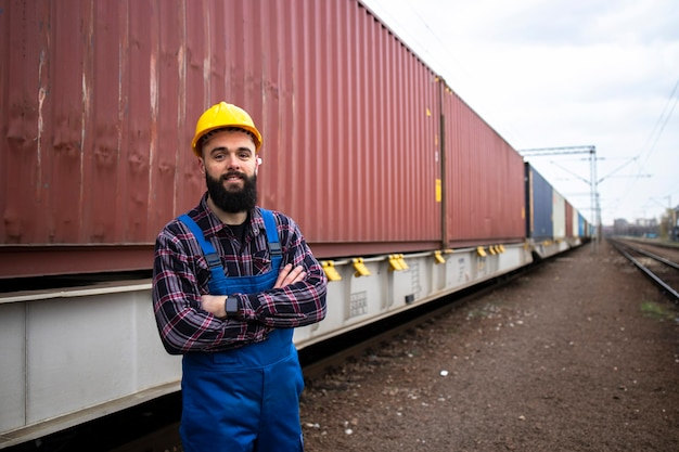 Portrait of worker at freight train station dispatching cargo containers for shipping companies