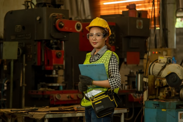 Portrait of a worker in the helmet working at factory with various metalworking processes