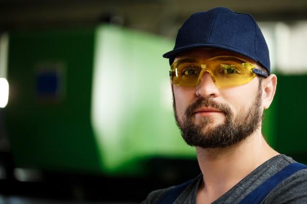 Portrait of worker in overalls, steel factory background.
