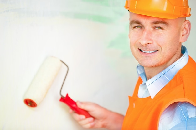 Portrait of a worker paints a wall roller for painting