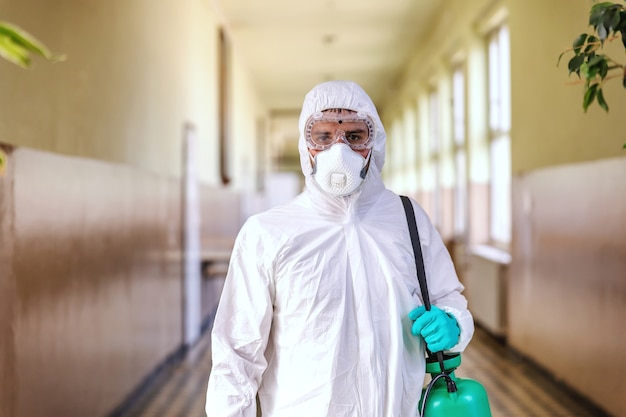 Portrait of worker in sterile white uniform, with face mask and rubber gloves on standing in hallway in school and holding sprayer with disinfectant