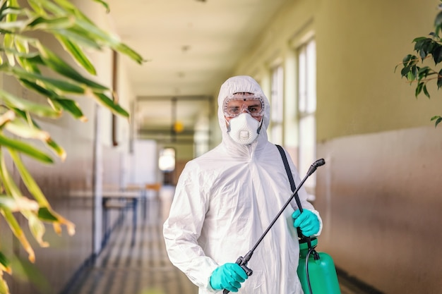 Portrait of worker in sterile white uniform, with face mask and rubber gloves on standing in hallway in school and holding sprayer with disinfectant.