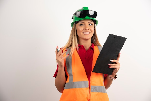 安全制服と白い背景の上に立っているゴーグルを身に着けている肖像画労働者の女性業界。