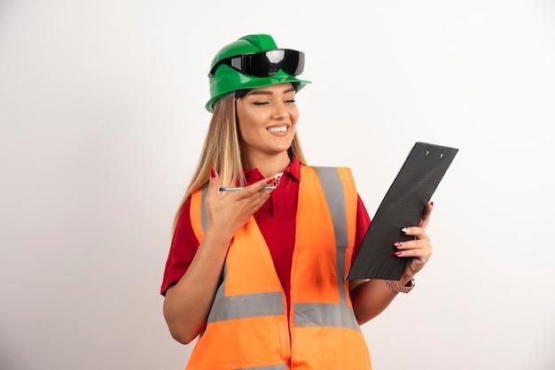 Ritratto lavoratore donna industria indossando uniformi di sicurezza e occhiali in piedi su sfondo bianco.