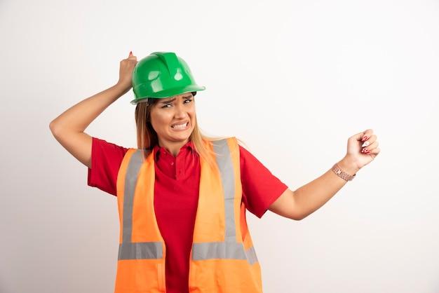 Портрет женщины индустрии работника нося форму безопасности представляя стоя на белой предпосылке.