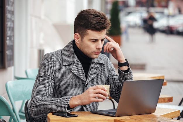 Portrait of working man sitting with silver laptop in cafe outside, drinking americano from glass