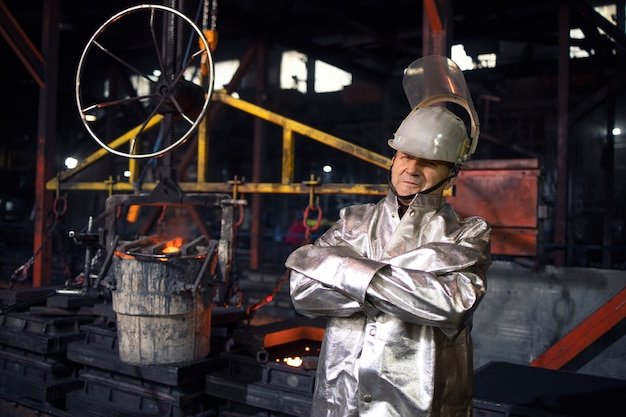 Portrait of workman in aluminized high temperature protection suit with arms crossed standing in foundry steel production factory.