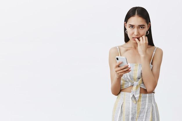 Ritratto di preoccupata affascinante ragazza abbronzata con i capelli scuri, mordere le unghie e guardare con espressione colpevole e preoccupata, tenendo lo smartphone, commettendo un errore enorme