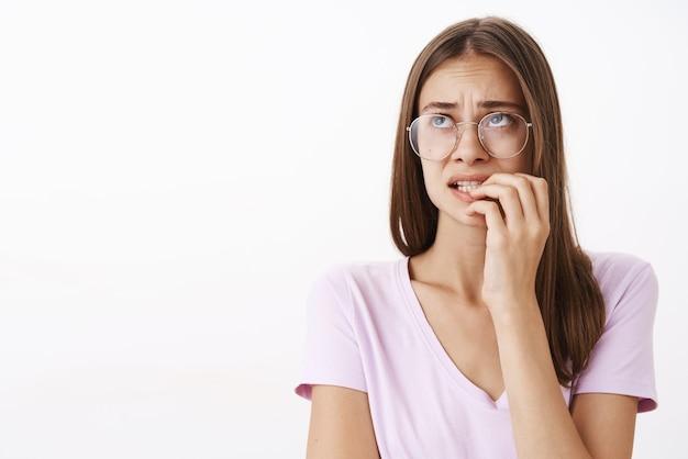 Ritratto di preoccupato e preoccupato carino donna in preda alla disperazione mordere le unghie accigliato guardando in alto a sinistra turbato con gli occhiali