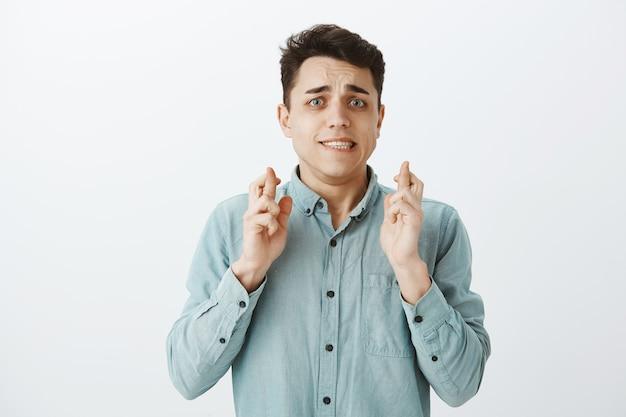 Portrait of worried doubtful caucasian guy in shirt