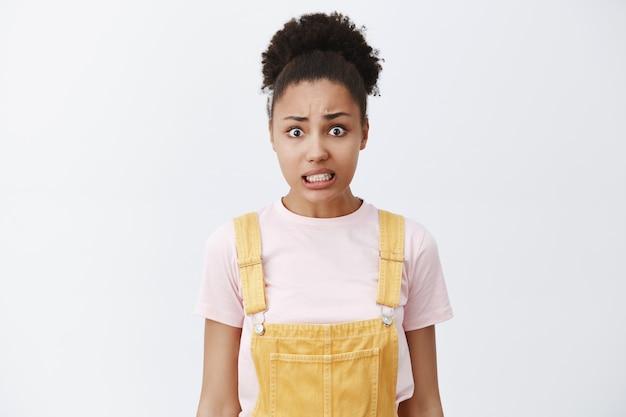 Ritratto di donna attraente insicura preoccupata con pelle scura e capelli ricci in acconciatura panino, serrando i denti, rendendo espressione colpevole