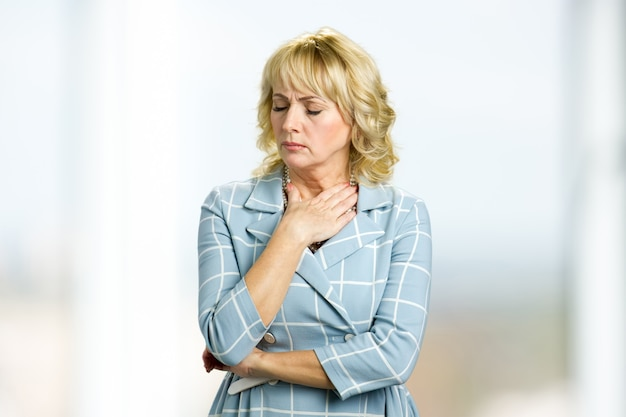 Portrait of worried mature woman. adult lady holding hand on neck and close eyes, painful feelings.