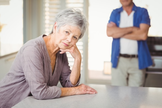 Portrait of worried senior woman with man standing